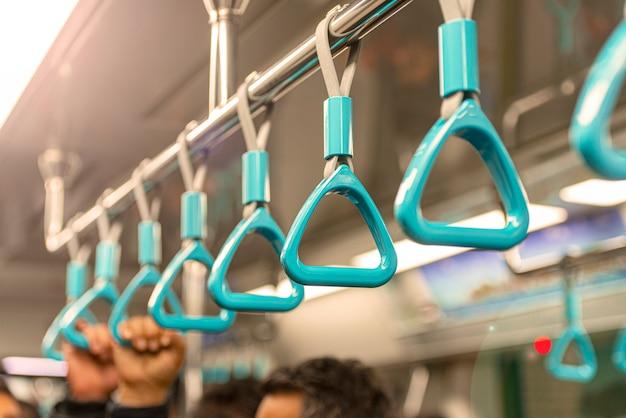 Close-up metro of metro leuning, hand met blauwe leuning