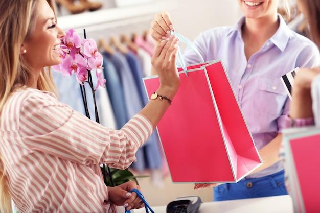 Close-up middengedeelte van vrouwelijke klant die boodschappentassen ontvangt in boetiek