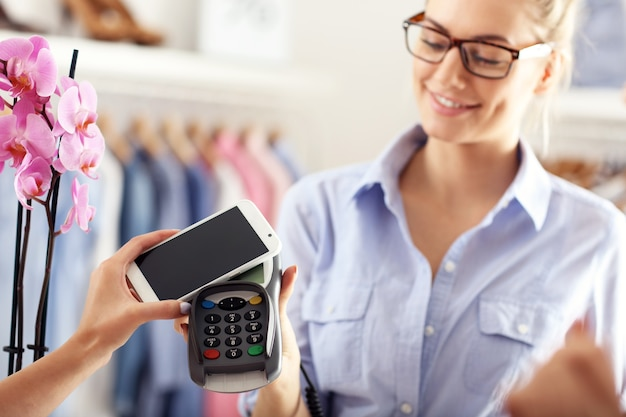 Close-up middengedeelte van vrouwelijke klant die in winkel betaalt met creditcard