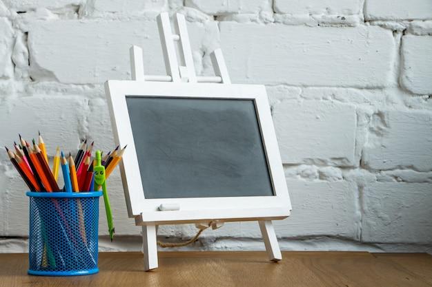 Close-up miniatuurschoolbord en tribune met schoolkantoorbehoeften op een witte bakstenen muur