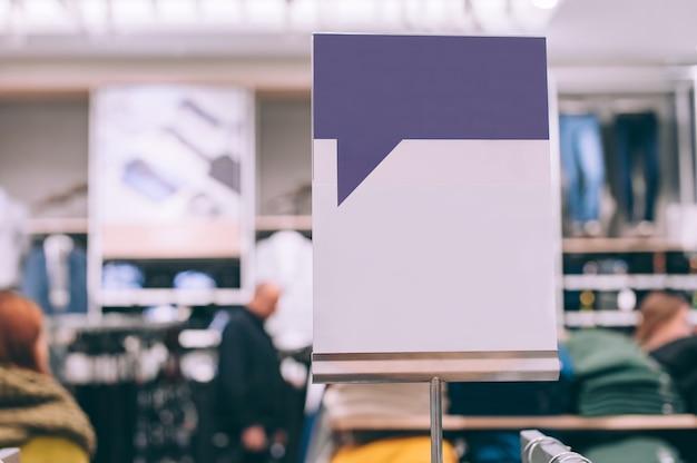 Close-up, mock up van een wit bord op de achtergrond van een winkel met kleding.