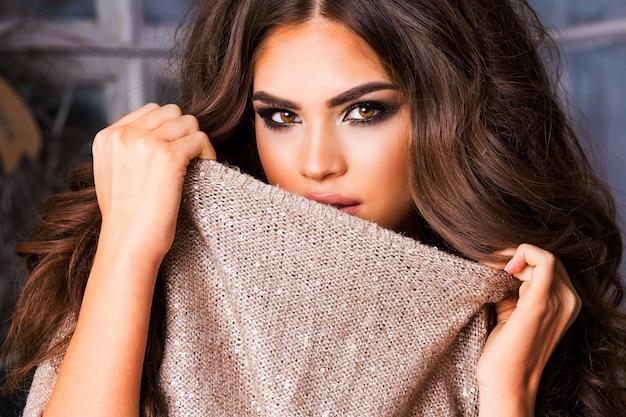 Close-up mode portret van geweldige elegante charmante vrouw met lichte make-up in warme trui over lichte kerstmis achtergrond