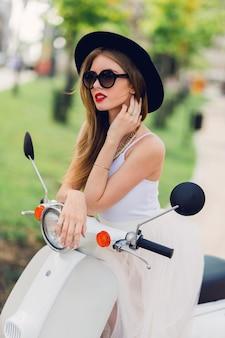 Close-up mode portret van jonge blonde vrouw in witte tule rok en zwarte hakken zittend op vintage scooter.