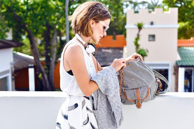 Close-up mode portret van jonge hipster mooie vrouw, iets zoeken in haar rugzak, wandelen en plezier maken op het dak, stijlvolle streetstyle outfit.