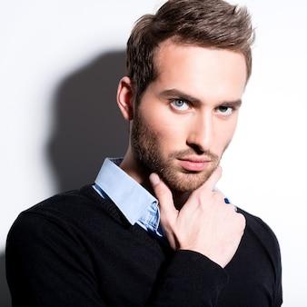 Close-up mode portret van jonge man in zwarte trui vormt over muur met contrast schaduwen.