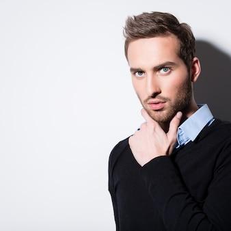 Close-up mode portret van jonge man in zwarte trui vormt over muur met contrast schaduwen