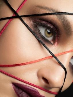 Close-up mode portret van jonge mooie vrouw met moderne trendy make-up. donkerrode smokey eyes en lippen.