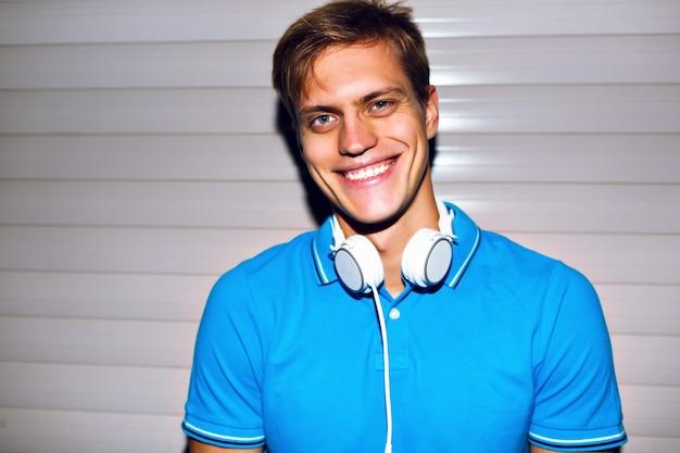 Close-up mode portret van knappe jongen helder blauw shirt, hipster bril en grote witte koptelefoon dragen,
