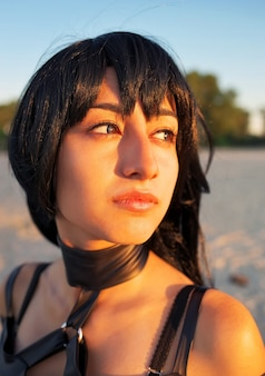 Close-up mode portret van mooi sensueel meisje met heldere sexy oog make-up look poseren in de zon, op het strand. cosplay origineel karakter