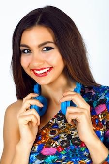 Close-up mode portret van prachtige jonge vrouw met heldere sexy make-up, heldere top en grote blauwe dj koptelefoon dragen.