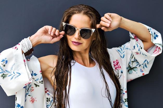Close-up mode zomer portret van prachtige brunette vrouw die zich voordeed op een grijze achtergrond, lange natte haren na het zwemmen