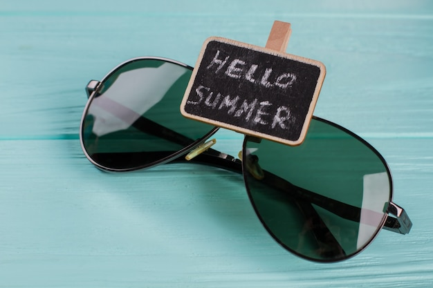 Close-up mode zonnebril op blauwe houten tafel. schoolbord met hallo zomer.