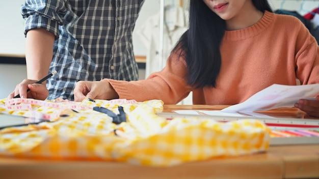 Close-up modeontwerper die met schetspapier werkt op stijlvolle vergadertafel.