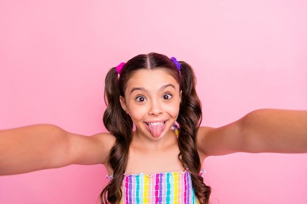 Close-up mooie grappige kleine dame twee staarten maken selfie stick tong