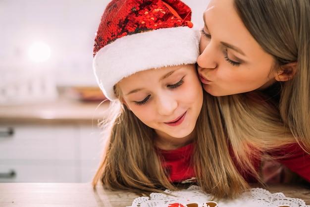 Close-up mooie jonge moeder kust haar tienerdochter op de wang in de keuken