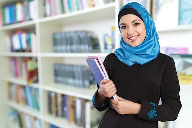 Close-up mooie jonge moslimvrouw met notebooks op onscherpe achtergrond