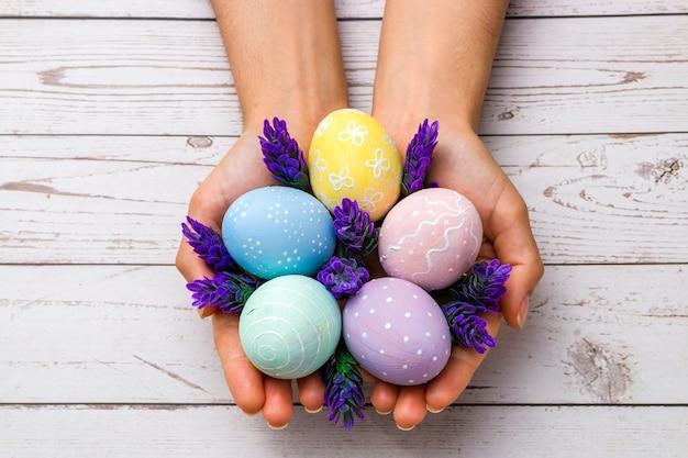 Close-up mooie vrouw handen met handgeschilderde paaseieren in tedere pastelkleuren en lavendel bloemen over houten tafel