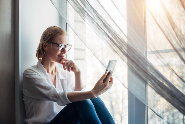 Close-up mooie vrouw zittend op een vensterbank thuis met smartphone ih haar hand. vrouwelijke online chat.