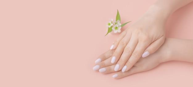 Close-up mooie vrouwelijke handen met bloemen op roze achtergrond. handverzorging, anti-rimpels, anti-verouderingscrème, spa