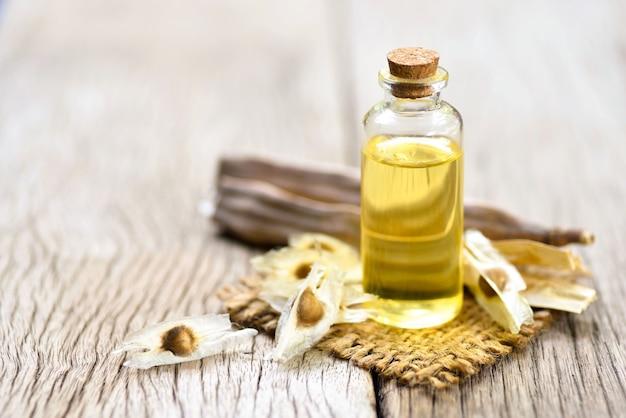 Close-up moringa-olie in glazen fles met gedroogde zaden en peulen op oud hout achtergrond.