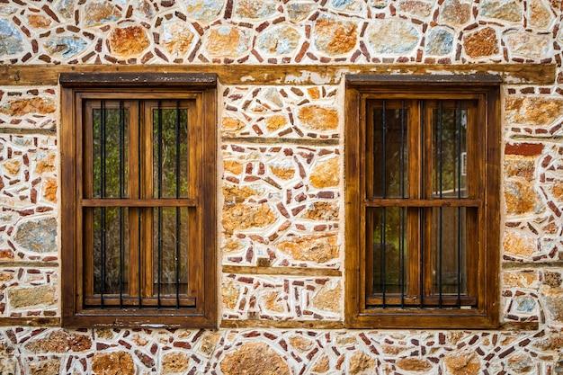 Close-up muur van een stenen huis met houten ramen en luiken. oude europese architectuur