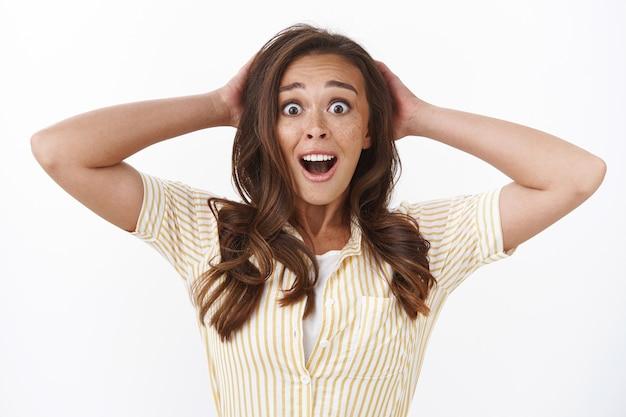 Close-up nerveus verraste jonge vrouw met sproeten, onverwacht nieuws ontvangen, naar adem snakkende kaak geschokt, hoofd verbijsterd grijpen, camera staren met opgetrokken wenkbrauwen van verbazing