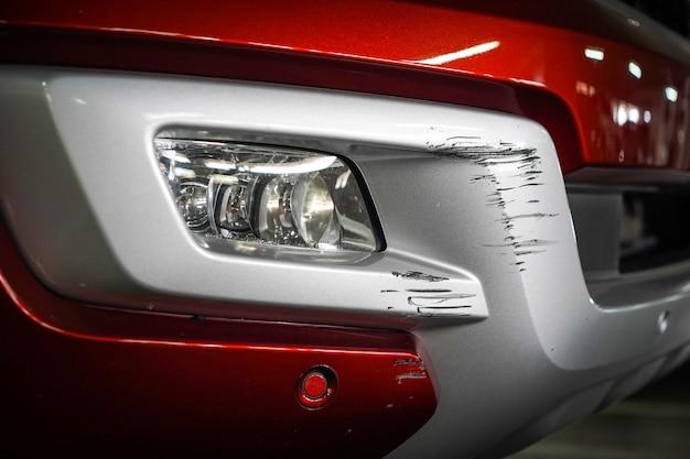 Close-up nieuwe krasschade aan de voorkant van de nieuwe rode auto.