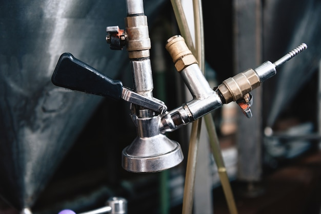 Close up of pipe system tap of stainless tank microbrewery.