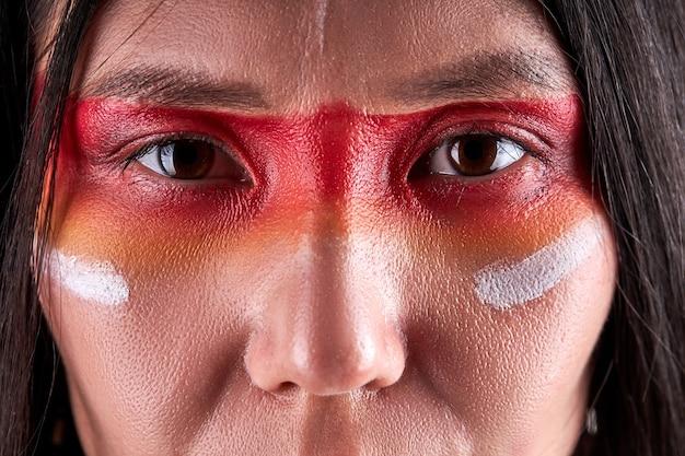 Close-up ogen van indiase vrouw zelfverzekerd ernstige etnische vrouw met schilderijen op gezicht. indiase etniciteit, sjamaanconcept