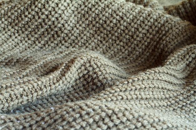 Close-up olijfkleurige gebreide trui gemaakt van natuurlijke wollen textuur, golvende plooien