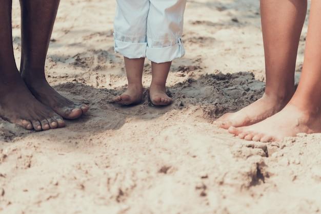 Close-up onderaan mening van afro-familie op sandy river beach.