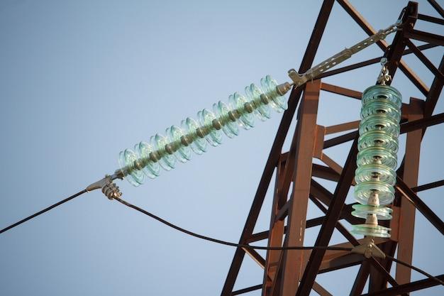 Close-up onderaanzicht van isolatoren op hoogspannings draden op een power tower tegen een blauwe hemel