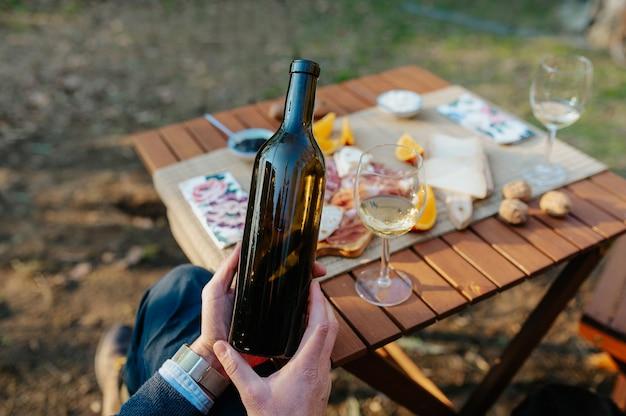 Close-up onherkenbare hand met een fles wijn. tafel met hapjes en lekker eten wijnproeven en picknick concept.
