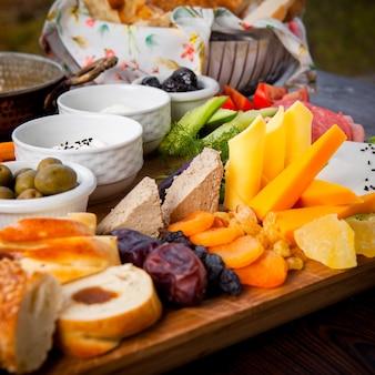 Close-up ontbijt verschillende soorten kaas, komkommers, tomaten, sla, gedroogde abrikozen, rozijnen, dadels op een houten sokkel