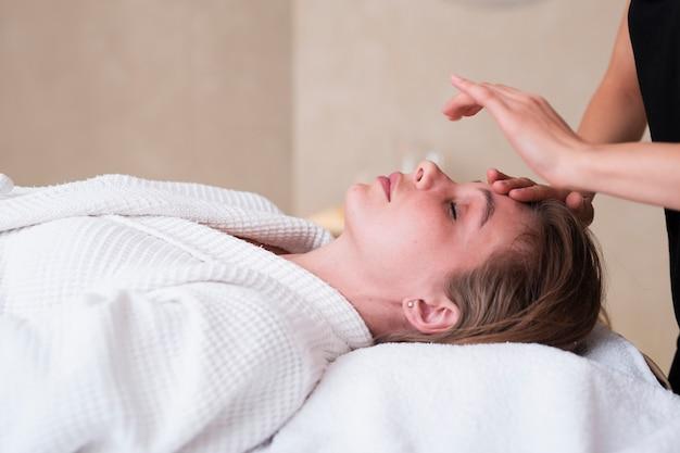 Close-up ontspannen vrouw die een gezichtsbehandeling krijgt