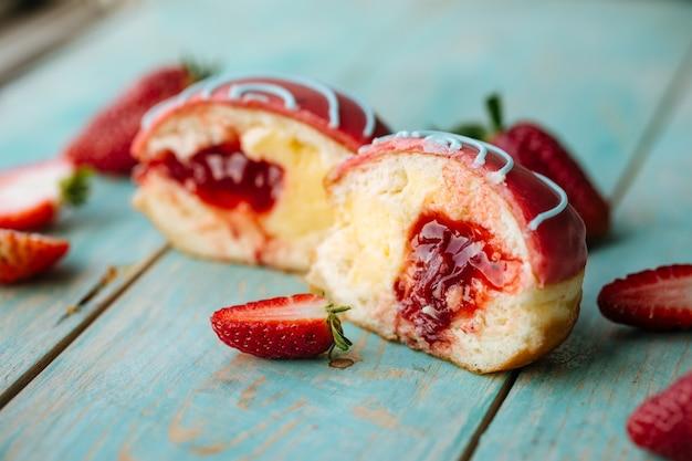 Close-up op aardbeivulling geglazuurde doughnut op turkoois houten