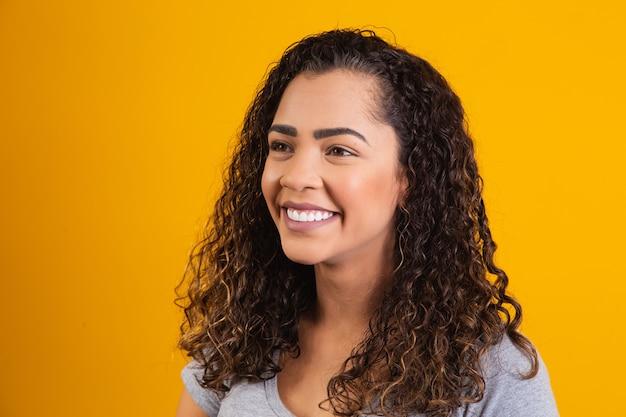 Close-up op afro vrouw gezicht lachend op gele achtergrond met vrije ruimte voor tekst. afro-vrouw die lacht.