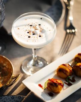 Close-up op alcoholische zure cocktail met een schuim op de gediende tafel