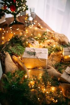 Close-up op ambachtelijke geschenkdoos op de houten tafel met garland en fir takken