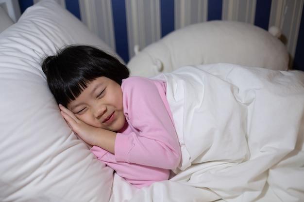 Close-up op aziatische jongen slapen op bed
