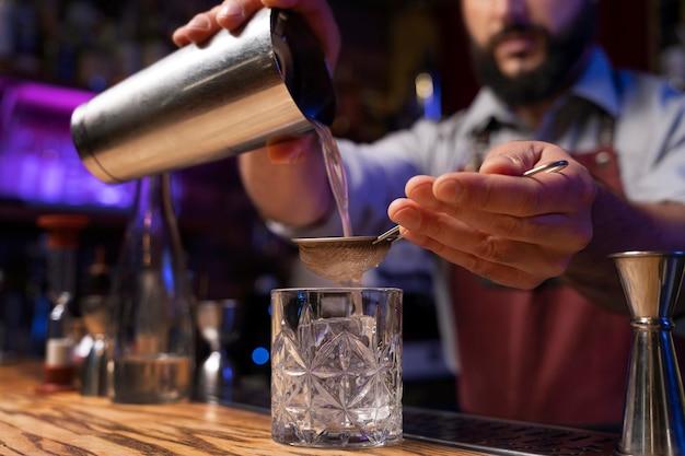 Close-up op barman en cocktailshaker