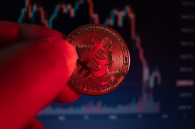 Close-up op bitcoin-munt met rode verlichting die verwijst naar vallende munt, zeer korte scherptediepte.