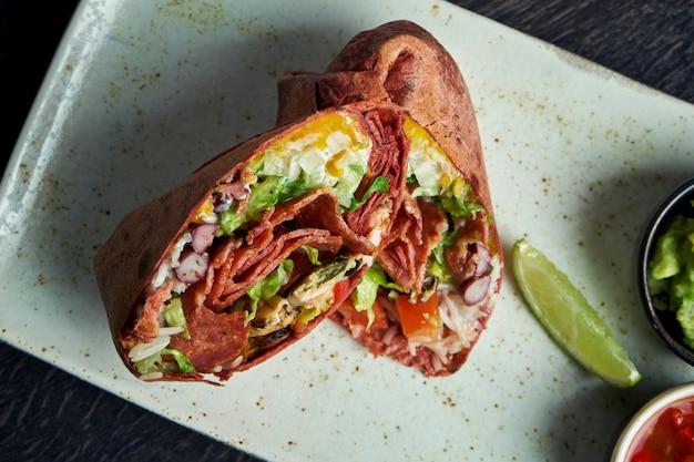 Close-up op burrito met salami chorizo, rijst, tomaten, maïs en paprika in bruin pitabroodje op een bruine plaat met tomatensalsa en guacamole. vegetarische shoarma roll