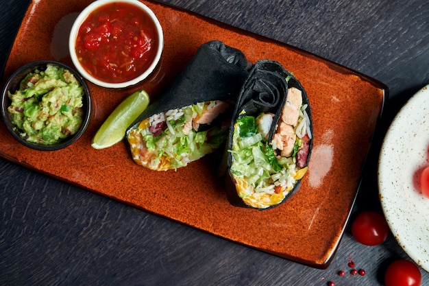 Close-up op burrito met zalm, sla, rijst, tomaten, maïs en paprika in zwarte pitabroodje op een bruine plaat met tomatensalsa en guacamole. vegetarische shoarma roll