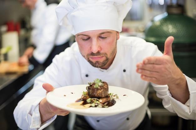 Close-up op chef-kok die het gerecht ruikt na het koken