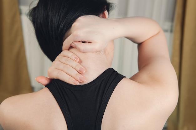 Close-up op de hand van een vrouw die haar nek masseert. de nek van het meisje doet pijn