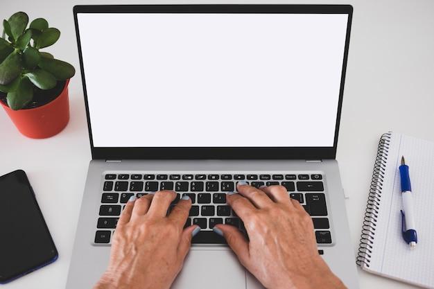 Close-up op de handen van de volwassen vrouw typen met behulp van laptopcomputer.