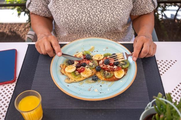 Close-up op de handen van de vrouw aan de cafétafel met bestek klaar om een gezond ontbijt te eten, klassieke amerikaanse pannenkoeken met banaan, kiwi, aardbei en honing. sinaasappelsap op tafel