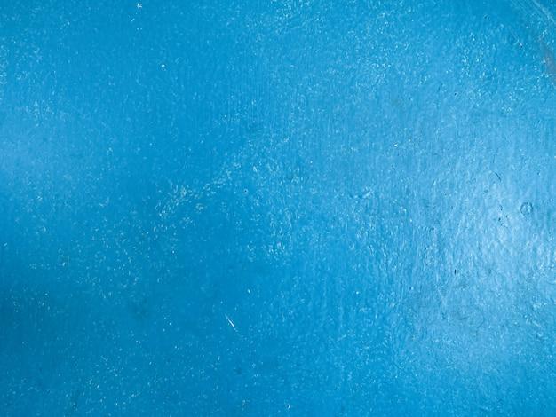Close-up op de mat geschilderde blauwe achtergrond van de oppervlaktetextuur