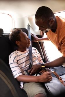 Close-up op de ouder die de veiligheidsgordel van de zoon vastzet